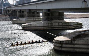 Een roeiboot vaart tussen de pijlers van de spoorbrug door.