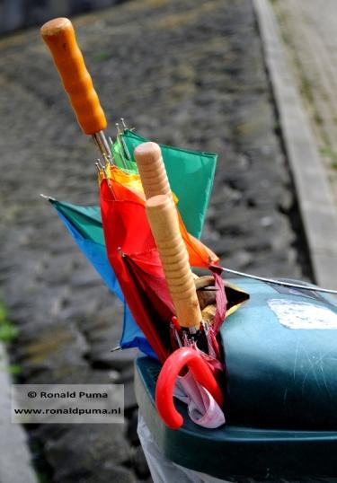 4 kapotte paraplu's in een afvalbak.