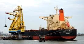 IJzererts wordt uit een groot schip overgeladen voor de staalfabriek.