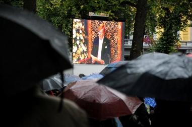 Onder een stortregen kijken toeschouwers naar de troonrede op een groot beeldscherm.