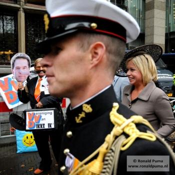 Minister Hennis Plasschaert van de VVD loopt langs een demonstrant.