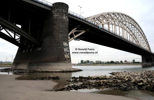 Waalbrug. Aan de witte aftekening op de pijler van de brug is de lage waterstand te zien.
