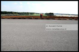 Nieuw wegdek. Op de achtergrond het stalen wegdek van de oude brug waarop beton wordt gestort.