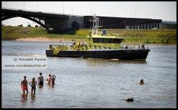 Rijkswaterstaat kijk toe, pootjebaden tussen de kribben mag, zwemmen in de Waal niet (boete 140 euro).