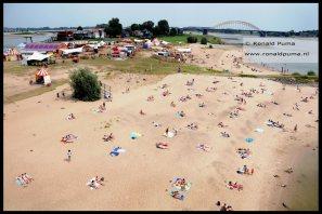 Aan de overkant van de Waal is Festival op 't Eiland met activiteiten, maar op het strand liggen kan ook.