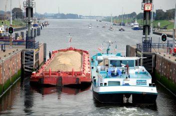 De kleine sluis met een schip met zand vaart richting Amsterdam.
