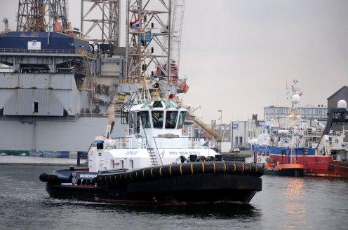 Sleepboot vaart de haven uit, op de achtergrond een boorplatform.