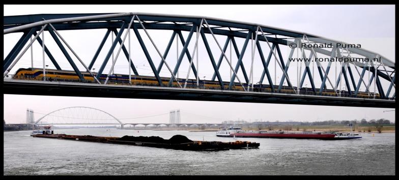 Schip geladen met kolen vaart over de Waal bij Nijmegen vanuit Rotterdam naar Duitsland.
