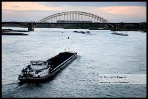 2 schepen geladen met kolen varen over de Waal bij Nijmegen richting Duitsland.