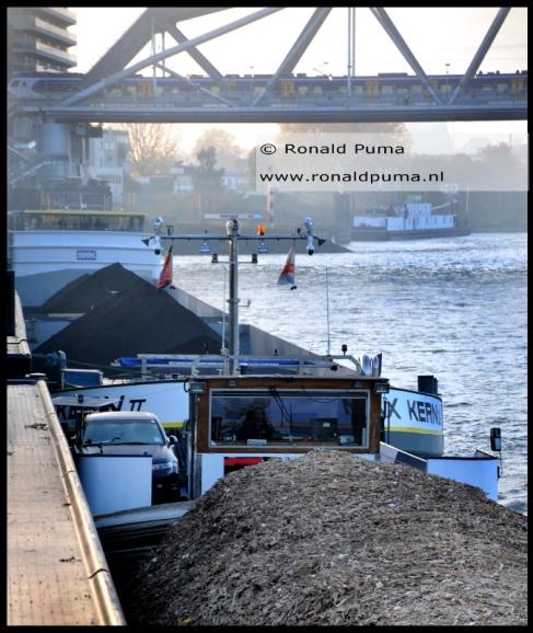 Op de voorgrond een schip met houtsnippers, ook wel bio-massa genoemd. Deze worden ook in energiecentrales opgestookt.