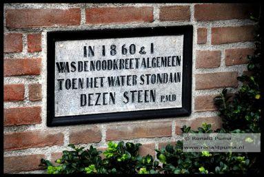 Gedenksteen in de benedenstad. In 1861 waren er nog geen goede waterkeringen. De Waal was bevroren geweest sinds december 1860. Doordat bij dooi in februari 1861 een watergolf ontstond kwamen water en ijsschotsen de benedenstad in tot meer dan 1 meter hoog. Er verdronken geen mensen omdat het niet onverwachts gebeurde. Men begon toen met betere waterkeringen.