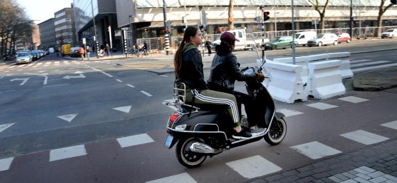 2 meisjes op een scooter.
