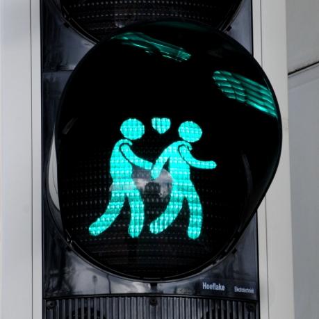 Een homoverkeerslicht boven een homozebrapad.