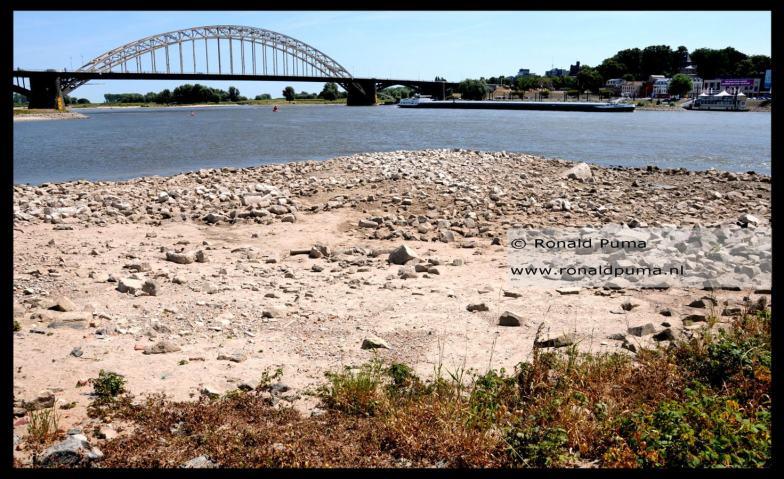 De waterstand van de Waal is laag, de rivierbedding met stenen is goed zichtbaar.