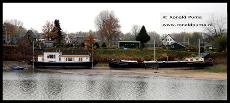 Woonark en woonboot liggen droog.