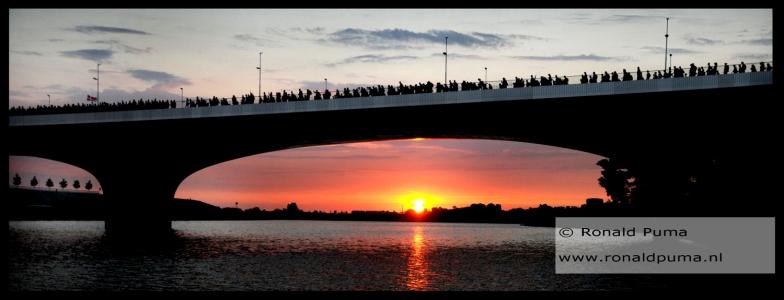 De zon komt op (05.45 uur). De morgen is fris en helder. Wandelaars lopen over de nieuwe brug over de Spiegelwaal richting Elst.