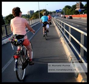 Wandelaars die om 07.30 uur beginnen met lopen fietsen richting het startpunt. Aan de overkant lopen de wandelaars de Waalbrug over.