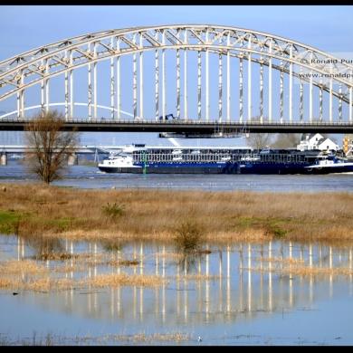 Op de voorgrond de oude Waalbrug die komende 2 jaar gerenoveerd wordt. Op de achtergrond de nieuwe brug met de naam De Oversteek (refereert aan de oversteek van soldaten tijdens WO2).