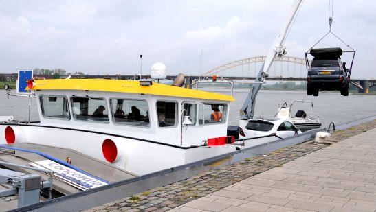Waalkade Nijmegen, een auto wordt op een schip geladen.