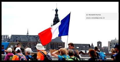 De wandelaars komen terug naar Nijmegen over de Waalbrug (15.07 uur). Achter de Nederlandse vlag de Stevenskerk.