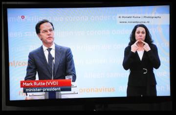 In de persconferentie werd medegedeeld dat de corona maatregelen nog geruime tijd zullen duren. Rechts de gebarentolk Irma Sluis.