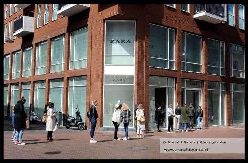 Doordat er een beperkt aantal mensen tegelijk een winkel binnen mag staat er een rij op straat in Nijmegen.
